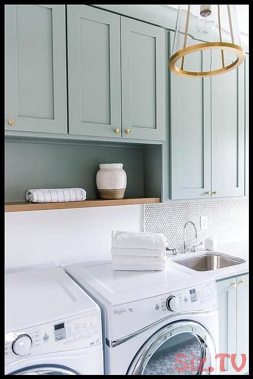 Exquisitely designed green gray laundry room is lit by a brass and glass lantern hung in front of green gray shaker cabinets accented with brass knobsExquisitely designed green gray laundry room is lit by a brass and glass lantern hung in front of green gray shaker cabinets accented with brass knobsBGI Design Save Images BGI Design Exquisitely designed green gray laundry room is lit by a brass and glass lantern hung in #accented #brass #cabinets #designed #exquisitely #front #glass #green #knobs #graylaundryrooms
