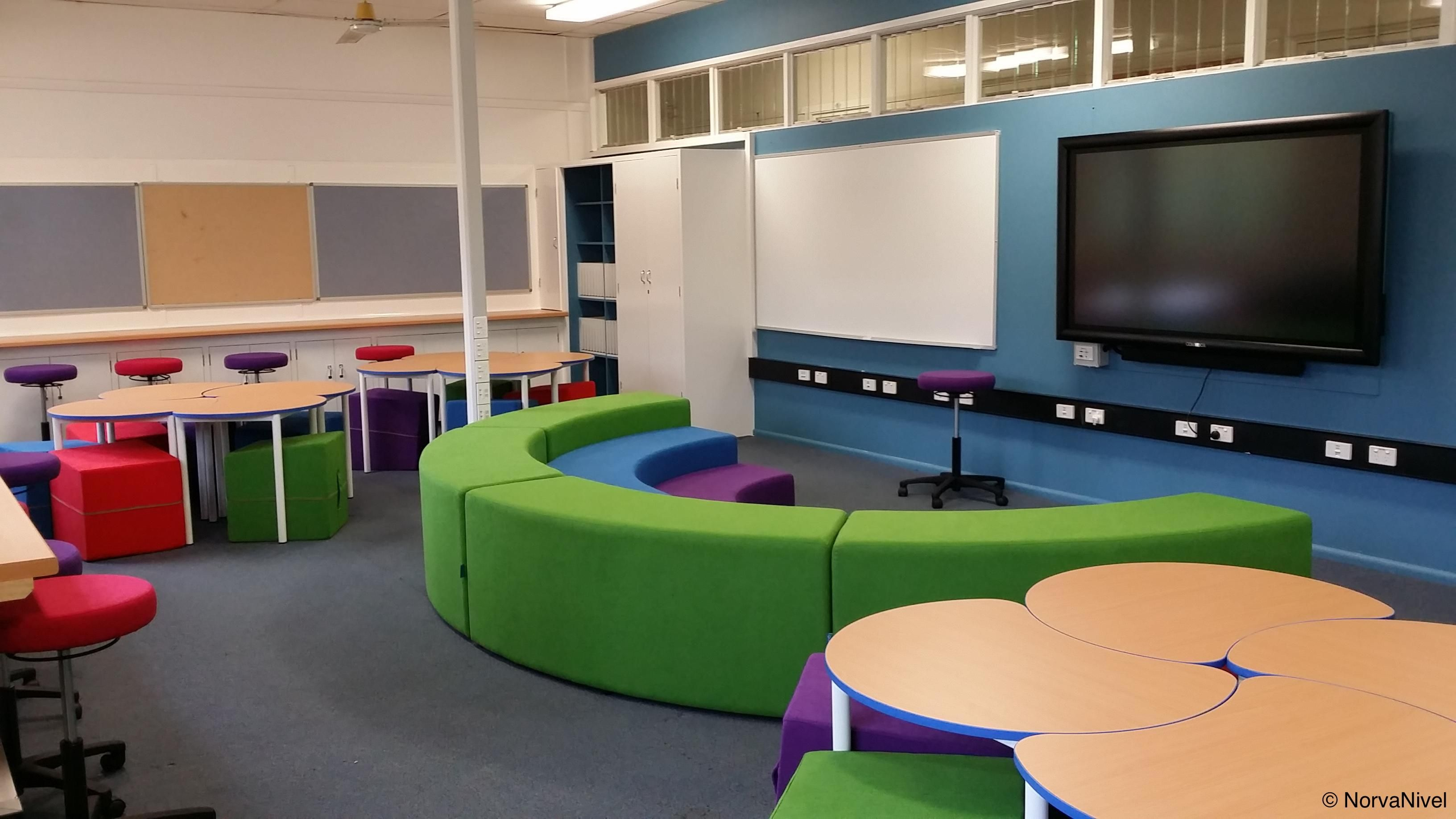 Colorful classroom with Rainbow tiered seating for group instruction and presentation and Pac tables with Miss-Shape ottomans.