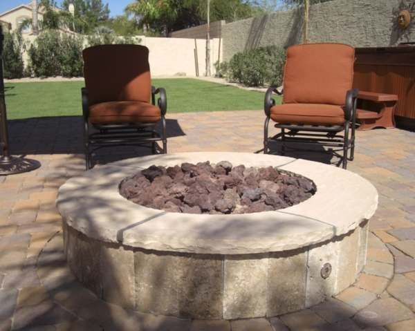A nice firepit area with a hot tub in the background.
