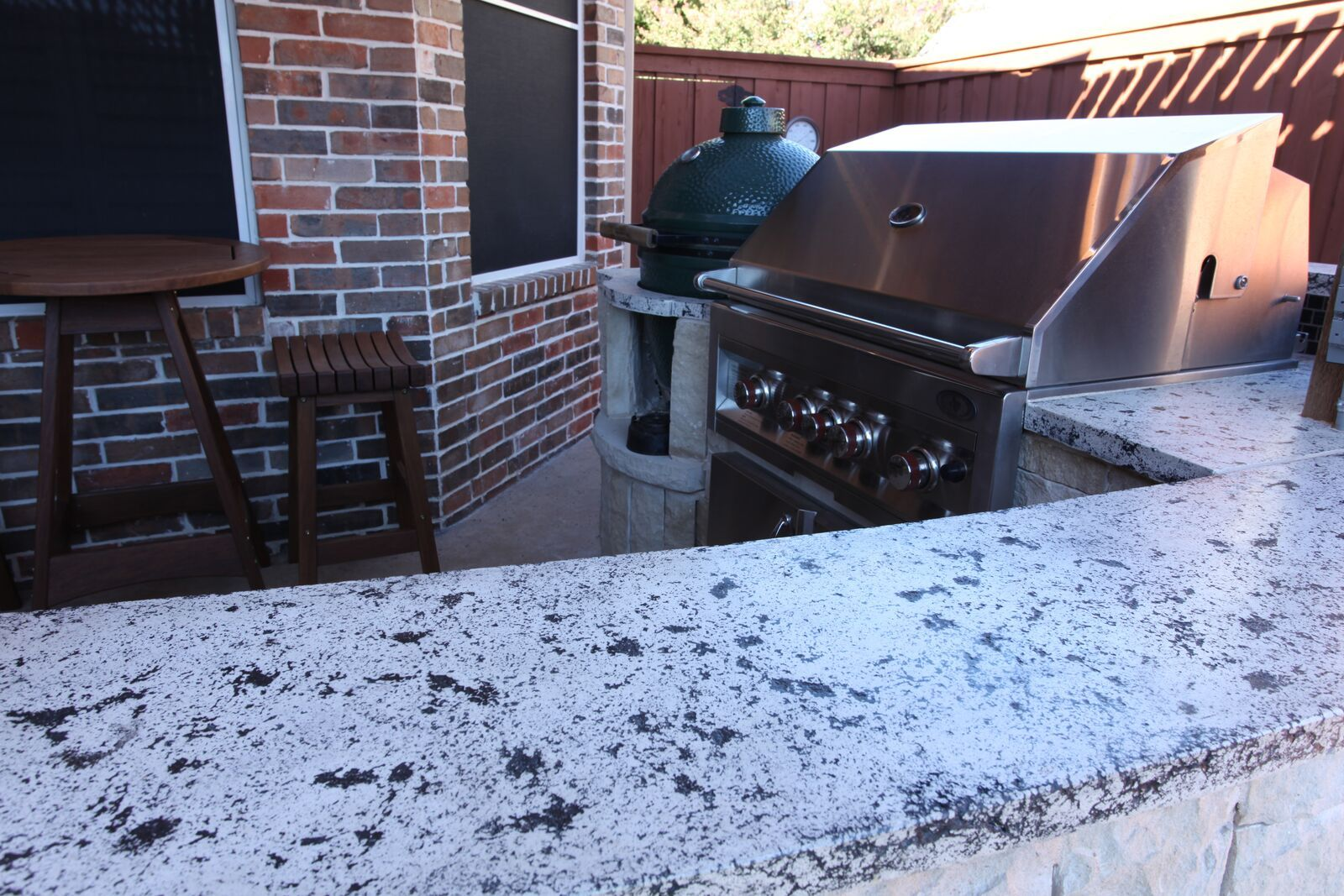 Lshaped outdoor kitchen with stainless bbq green egg and granite