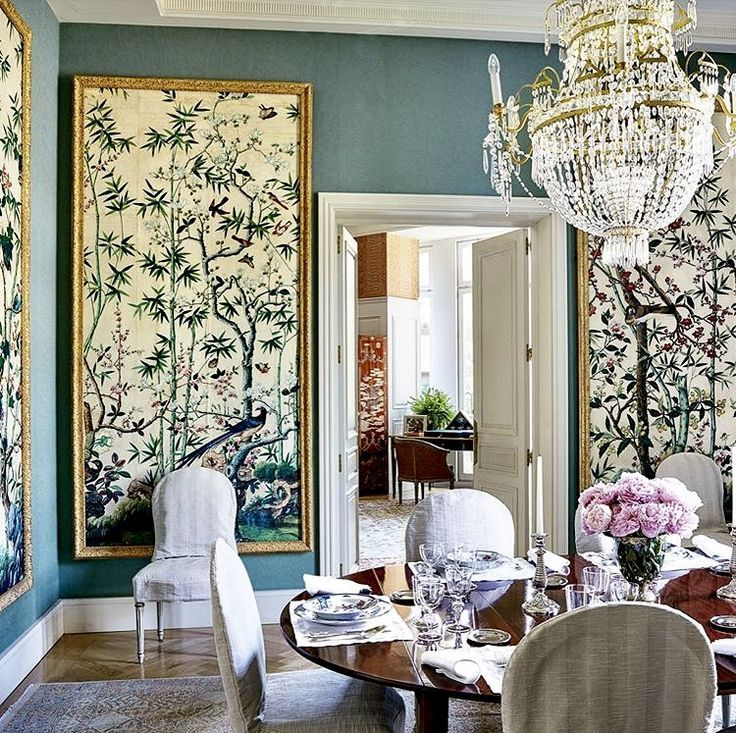 Design by Michael S. Smith with teal walls and beautiful Chinoiserie panels in a dining room.