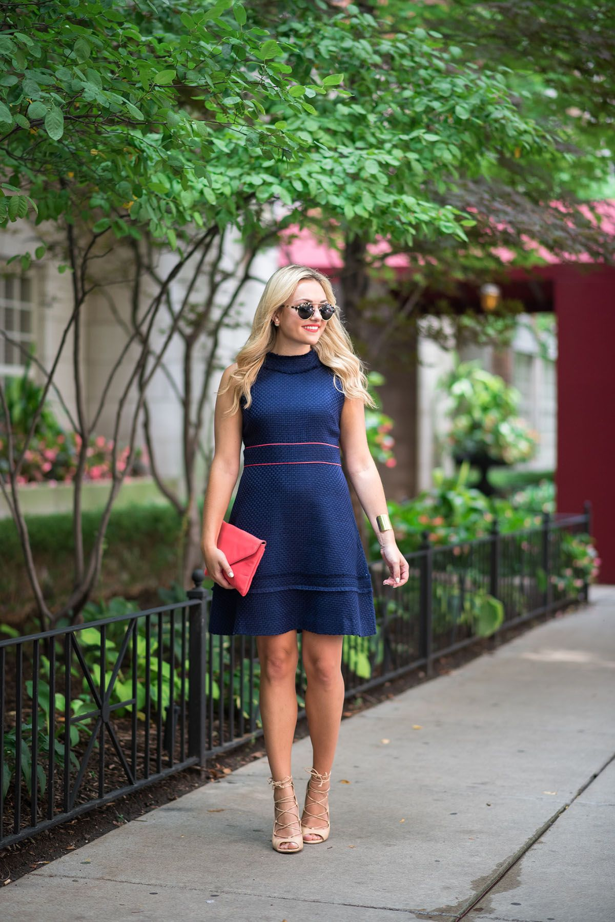 d45b48094d68 Fashion blogger Bows   Sequins wearing a navy blue and coral dress,  sunglasses, and coral clutch in Chicago.