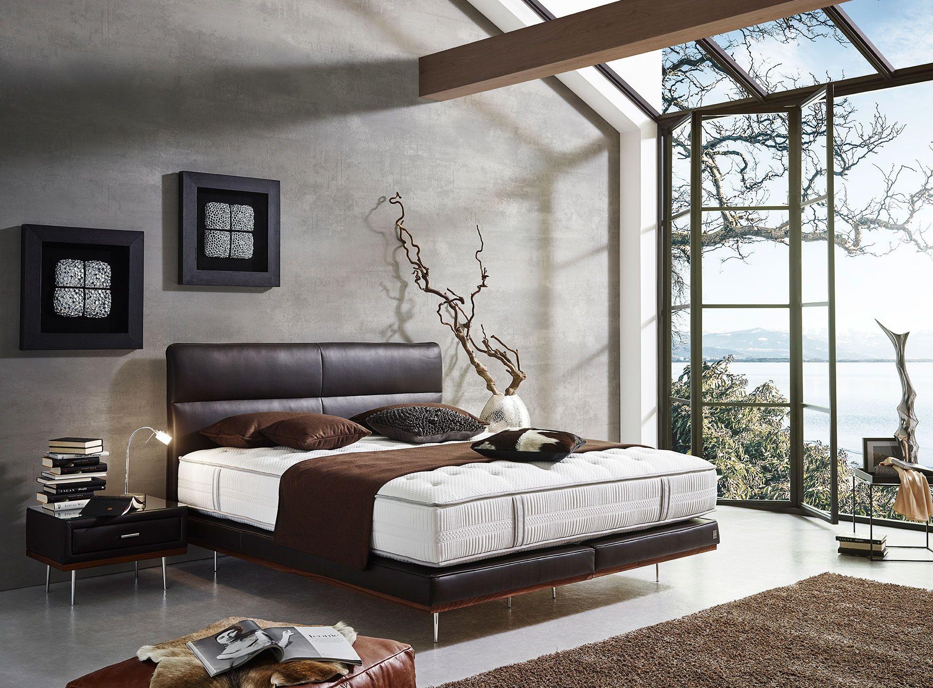 Mit einem aufregenden Kontrast aus kühlem Chrom, natürlichem Massivholzsockel und feinstem Lederbezug bringt Boxspringbett Thea einen edlen Touch ins Schlafzimmer.