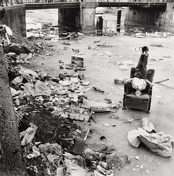 A boy is playing amidst rubbish on the frozen Brouwersgracht. Just visible in the background is the Oranjebrug (bridge 146) running over the canal, connecting Brouwersgracht and Binnen Oranjestraat. The photograph was taken by Frits Weeda in 1963. The boy – who stands on his head on a chair that ended up in the frozen canal – seems to be performing a circus act.
