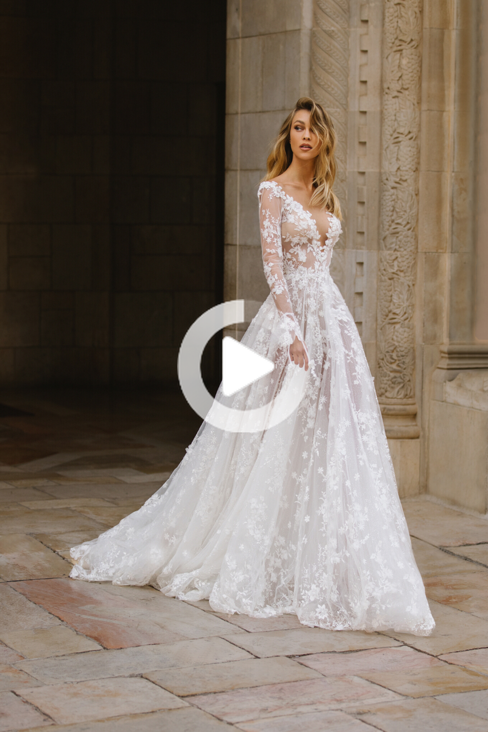 Romantic 3D embellishments scatter throughout this A-line gown with long fitted sleeves and deep plu...