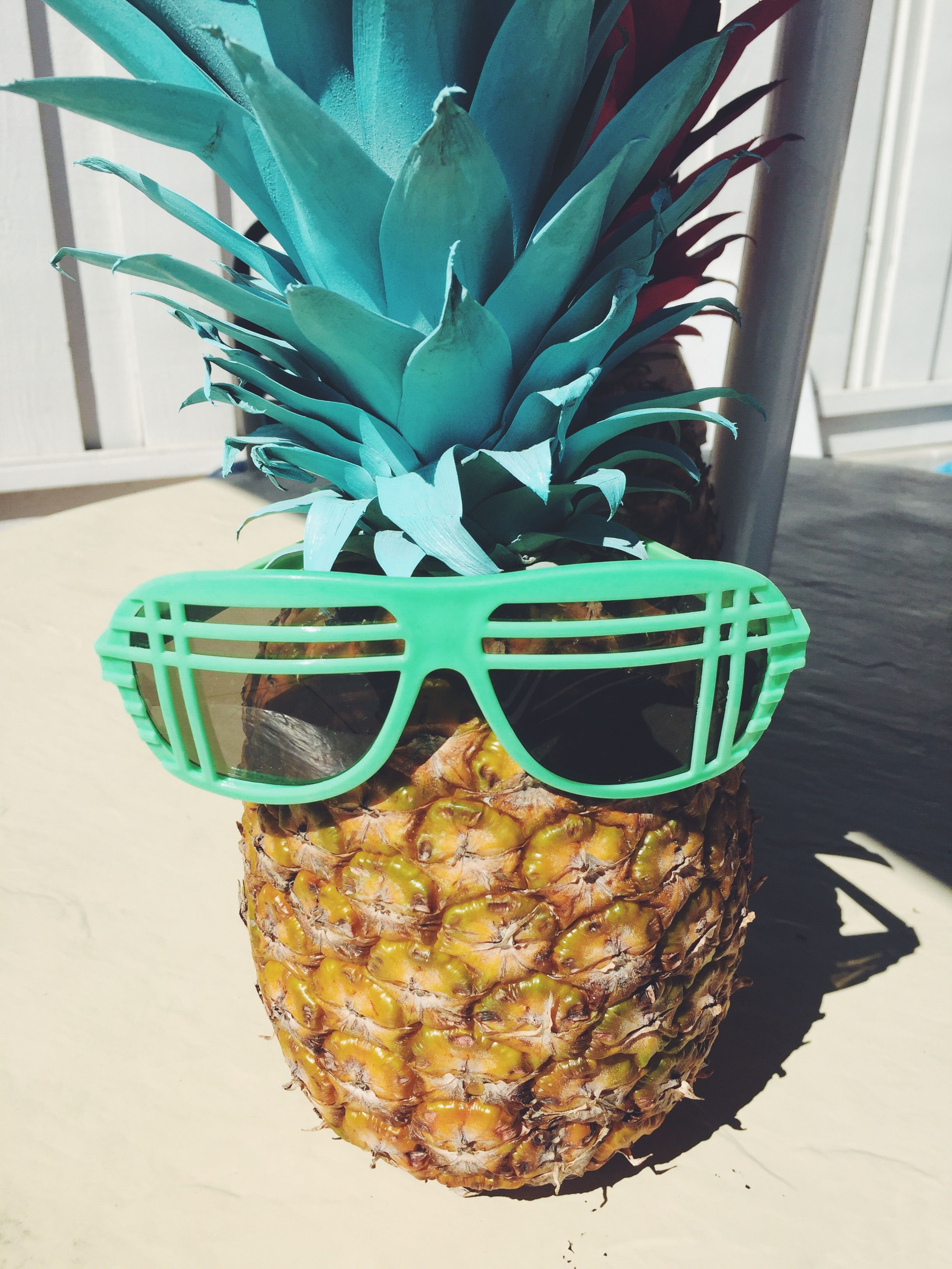 Pineapple party came to life by spray painting the tops of the pineapples different colors and adorning them with cool sunglasses.
