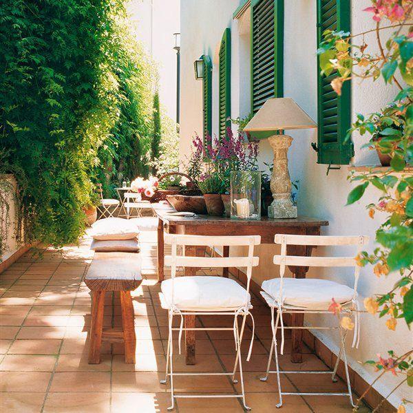 Patio con mesa de madera sillas de metal plegables for Materiales para patios exteriores