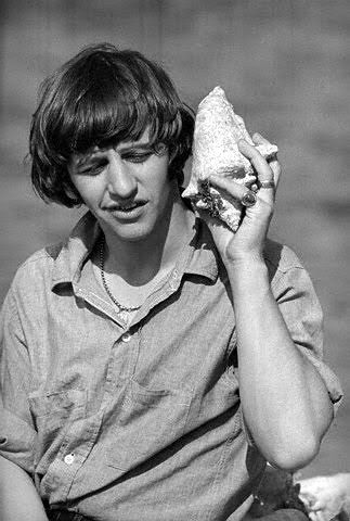 A cute shot of Ringo with a sea shell taken during the filming of Help! February 25,1965 Nassau, New Providence, Bahamas