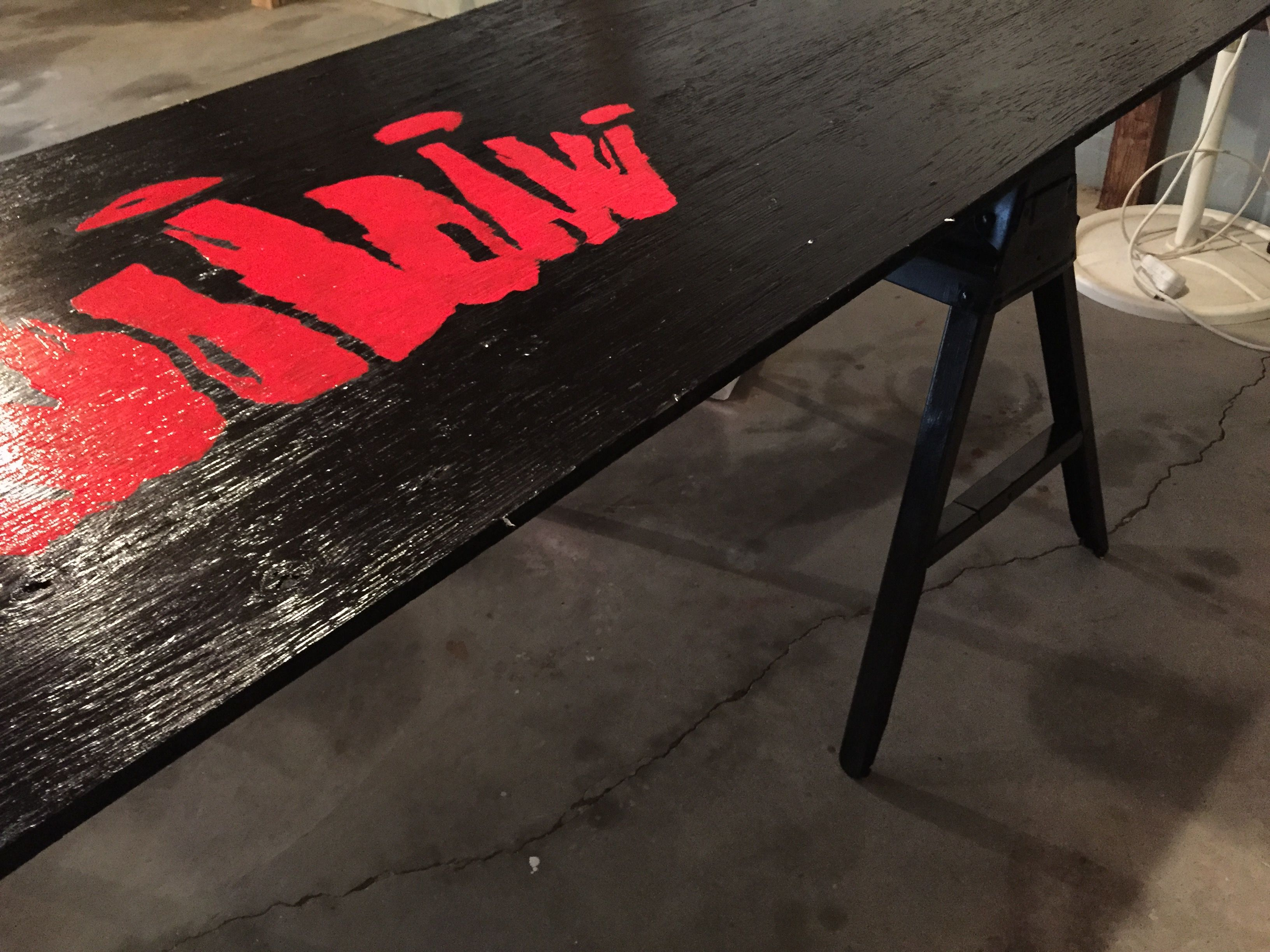 DIY beer pong table out of wood and paint. Saw horses for