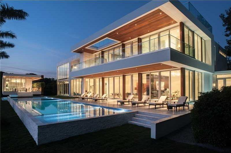 This Miami mansion has marbled walls, covered patio space, invisible glass railings, terraces, modern furniture, fireplaces, open interiors, walls of glass and a massive pool.