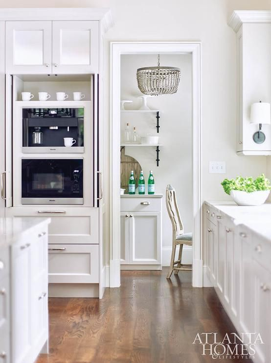 Lovely Kitchen Features A Wall Of Square Mirrored Cabinets Stacked Atop  Pantry Cabinets Hiding A Built