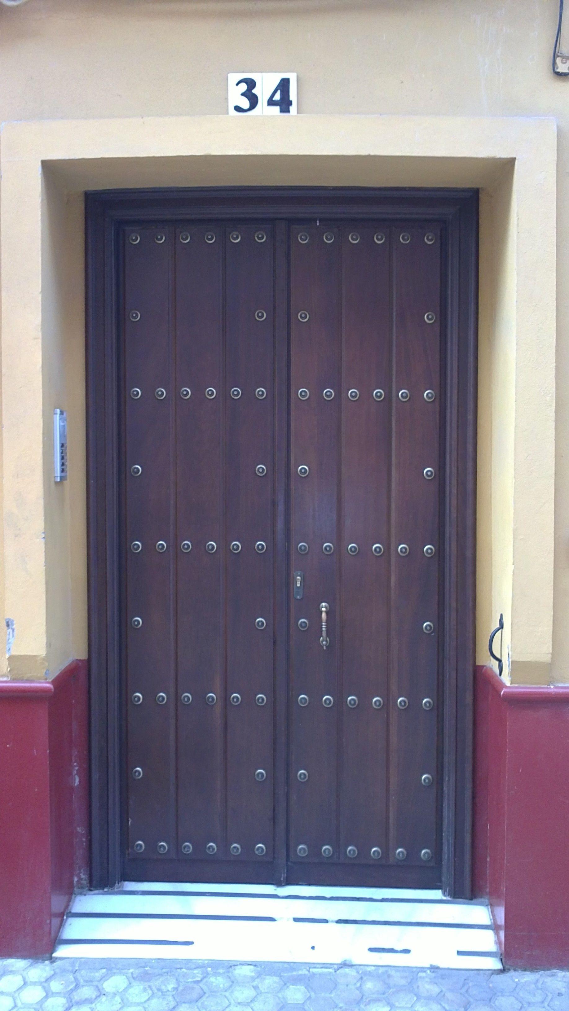 puerta doble en madera de iroko para exterior con duelas y clavos