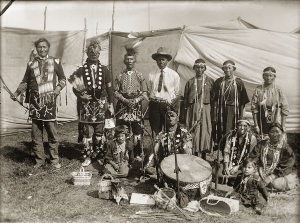 Ho-Chunk performers gathered behind a drum and Winnebago baskets at the 1908 Homecoming by Charles Van Schaick. Standing from the left are Jim Swallow (MaPaZoeRayKeKah), William Massey (ChawRoCooChayKah), George Eagle (WaNaKeeScotchKah), Benjamin Thundercloud (NySaGaShiskKah), and Flora Thundercloud Funmaker Bearheart (WaNekChaWinKah). The woman standing on the far right is Susie Lena Pettibone Johnson (ChoNukKaWinKah), and the woman seated to the left is Addie Littlesoldier Lewis Thunder (Kzunc
