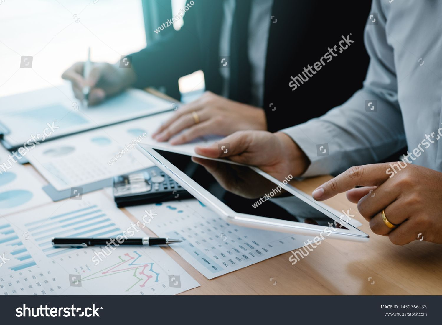 Managers are using tablets to analyze sales cost reports and explain summary reports to employees calculate and record summary information data in the office