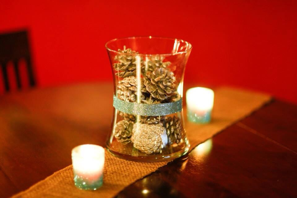 Silver spray painted/glittered pine cones in a glass jar with blue glitter ribbon wrapped around the center, glitter votives in glass containers sprayed with spray adhesive and rolled in glitter (winter wonderland bridal shower)