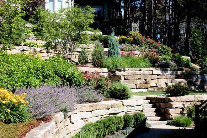 Terasovitá okrasná záhrada vo svahu s kamennými múrikmi