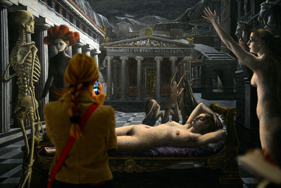 "A woman looks at the painting ""La Venus endormie"" by Paul Delvaux"