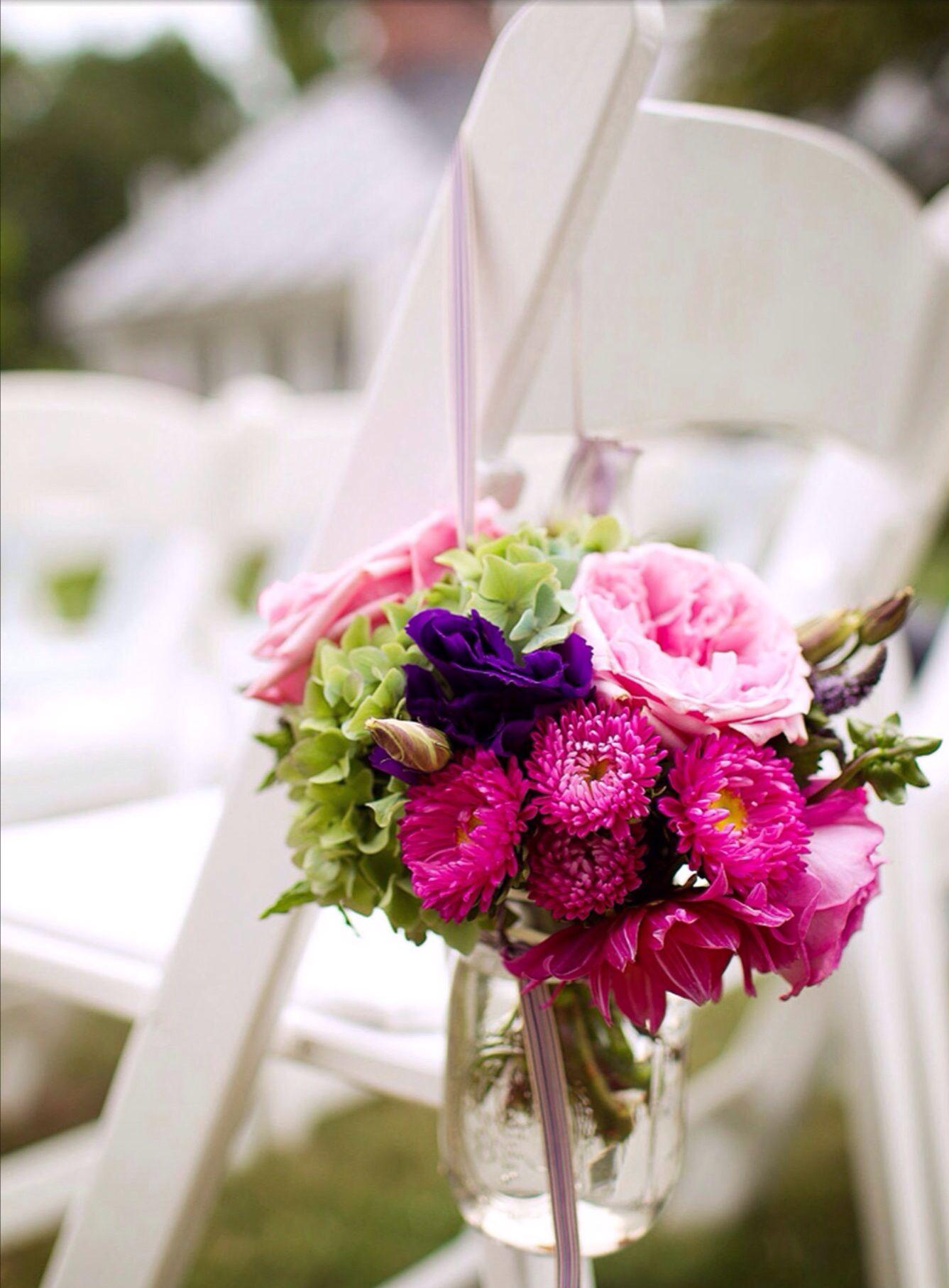 Ortensie verdi nel mazzetto ultra colorato di fiori che fanno da ornamento alla sedia da dentro al loro vasetto appeso