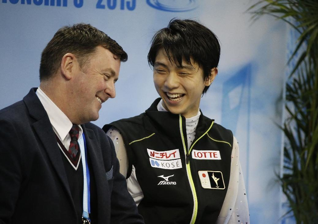Yuzuru Hanyu of Japan sits with his coach after his performance in the Mens Short Program event in the ISU World Figure Skating Championship 2015 held...