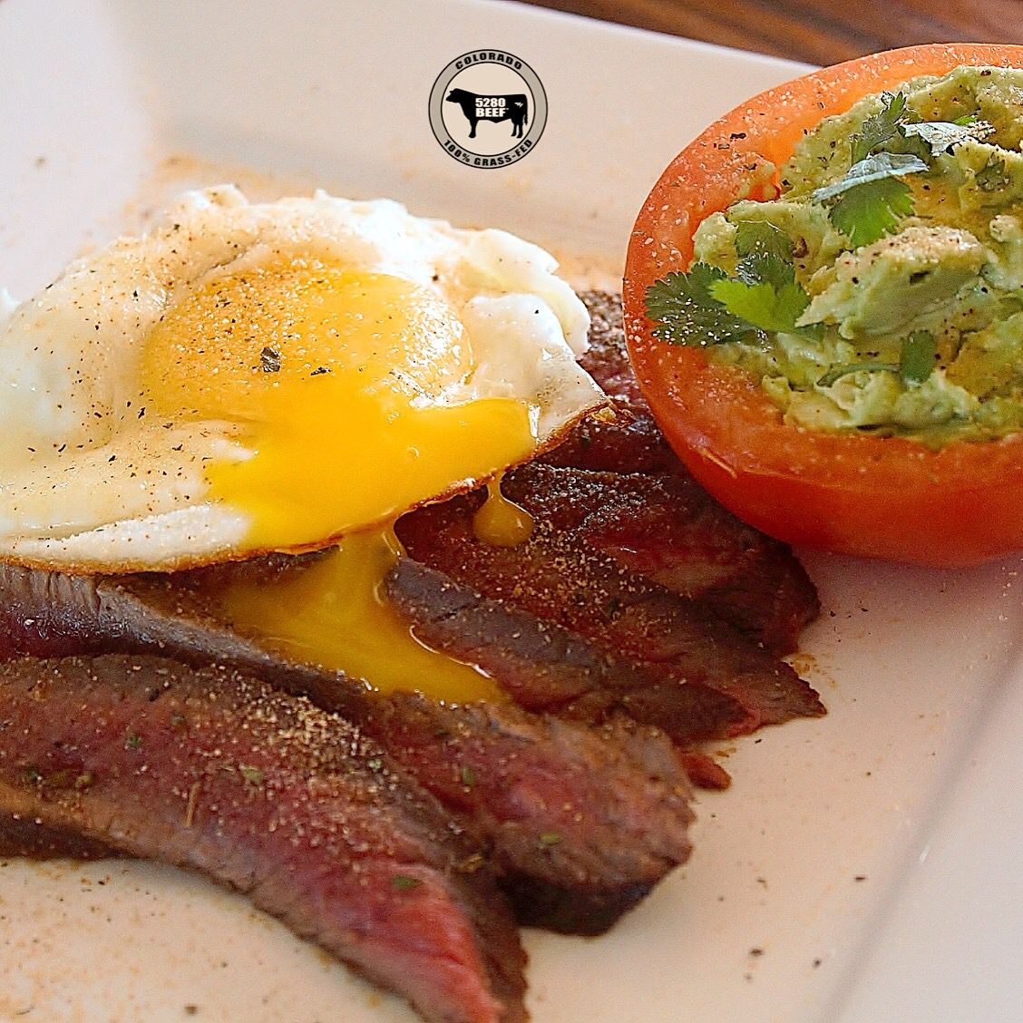 We marinated one of our 5280 Beef® Sirloin Tip steaks overnight in balsamic vinegar & @flavorgod Garlic Lovers seasoning. We seared the steak & cooked one of our farm-fresh eggs in @omgheebutter and added a guac stuffed tomato on the side. To top it off, we sprinkled more #flavorgod goodness and some fresh cilantro!