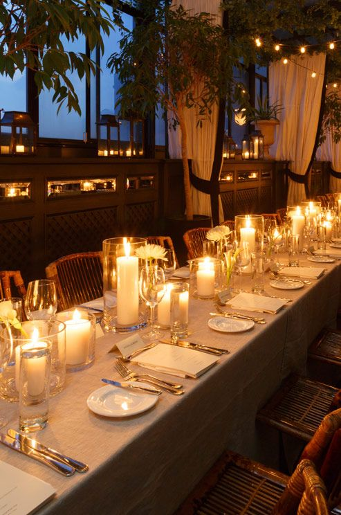 Small Votives In Lanterns Line The Perimeter While Pillar Candles Brighten Dining Table