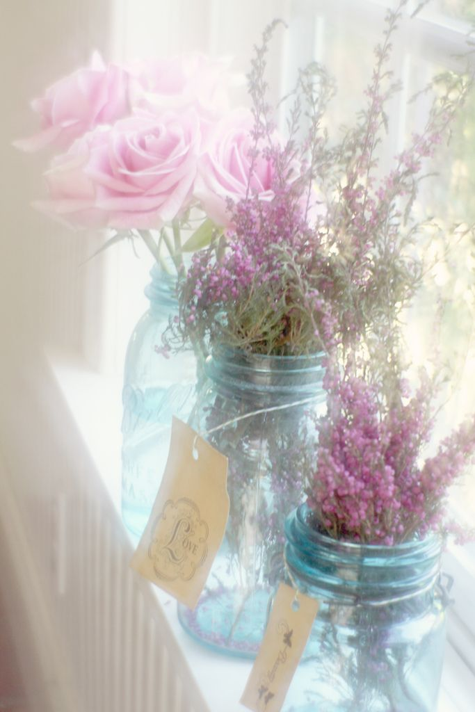 Lavender and roses in blue canning jars on a window sill
