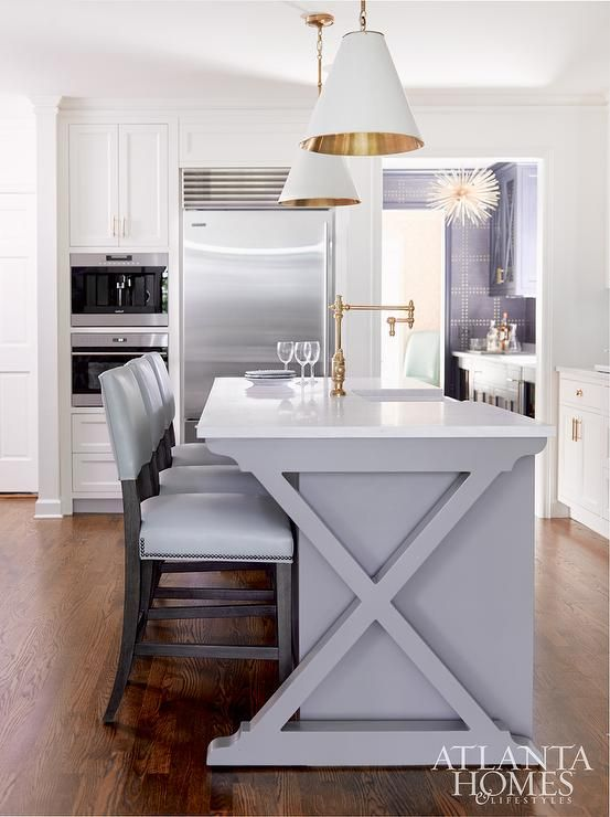 Two white and gold Goodman Hanging Lamps are hung over an x-based gray center island accented with a white quartz countertop seating light gray leather barstools and finished with a sink and vintage brass swing arm pot filler.