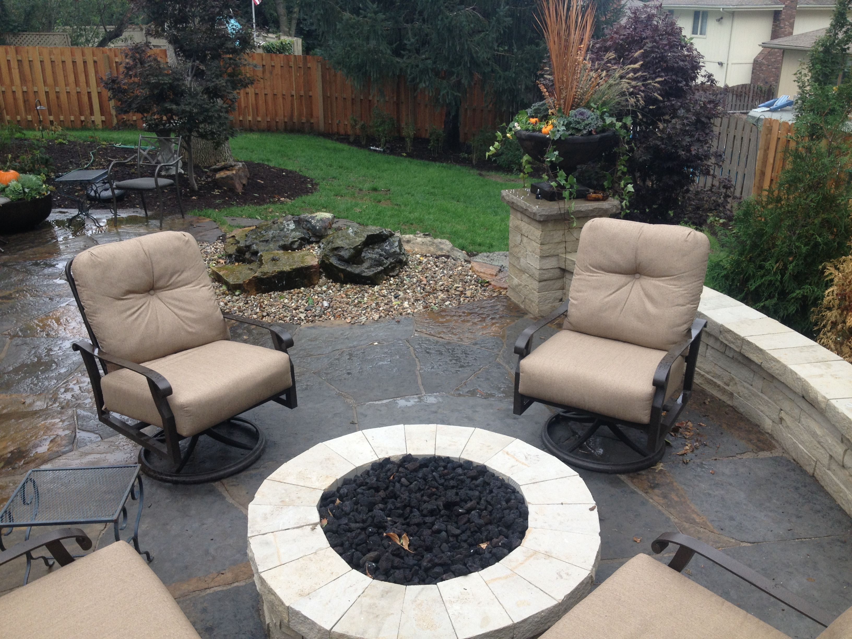 Blue Brown flagstone patio with natural stone seatwall and fire pit. Pillars for seasonal containers and a water feauture. By Greenlife Gardens