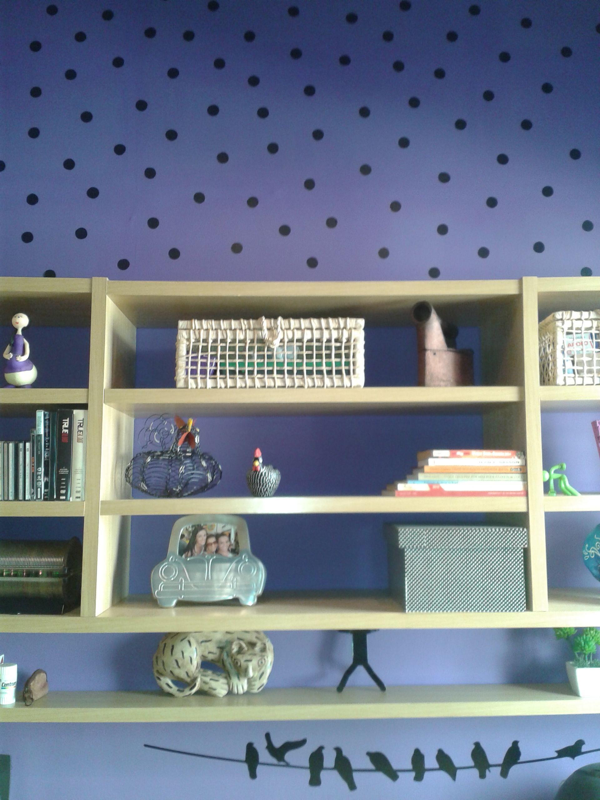 Neste quarto tem uma estante e bancada planejada. Acima da estante bolinhas de contact