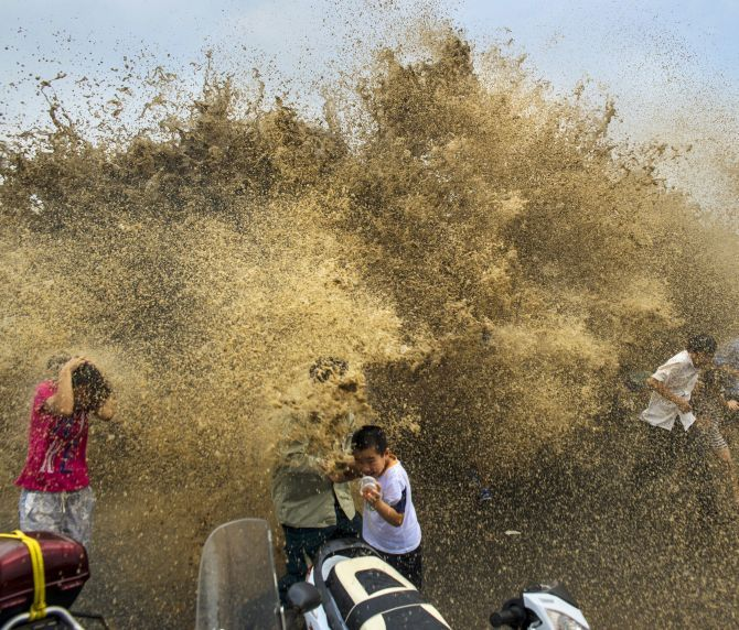 Visitors run away from waves from a tidal bore as it surges past a barrier on the banks of Qiantang River, in Hangzhou Zhejiang province, August 25