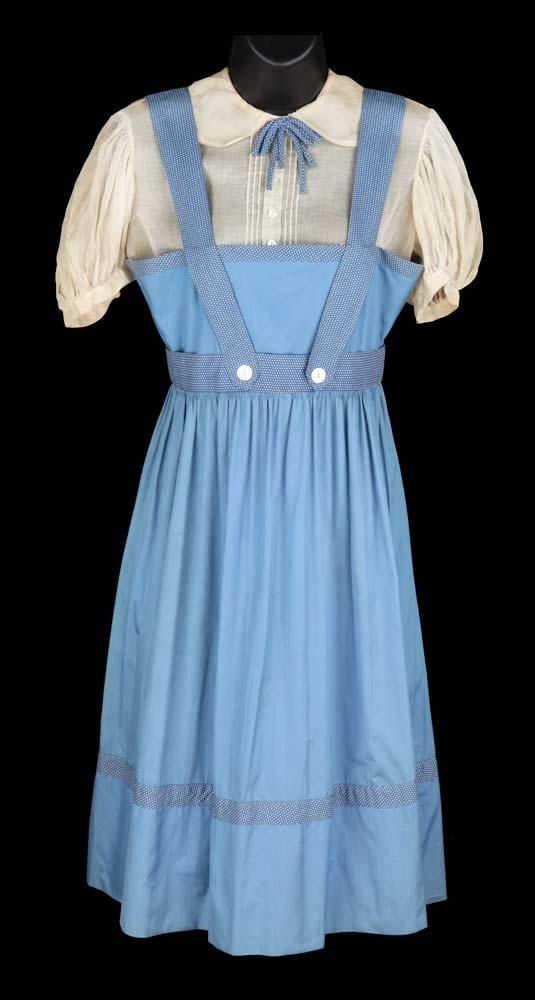"Judy Garland ""Dorothy Gale"" blue cotton test dress with polka dot trim and ivory sheer puff-sleeved blouse by Adrian from The Wizard of Oz. (MGM, 1939) Ivory sheer puff-sleeved blouse with blue ribbon. No label. Blue cotton pinafore with polka dot trim. Handwritten label ""Judy Garland 3955."" Worn by Judy Garland as ""Dorothy"" in the first two weeks of filming in The Wizard of Oz."