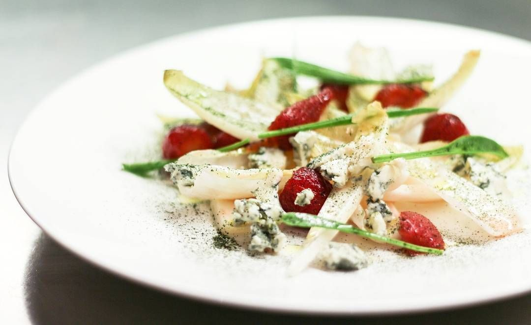 Salad of fresh strawberries, endive, blue cheese, walnuts and chives. Topped with ground dried parsley.