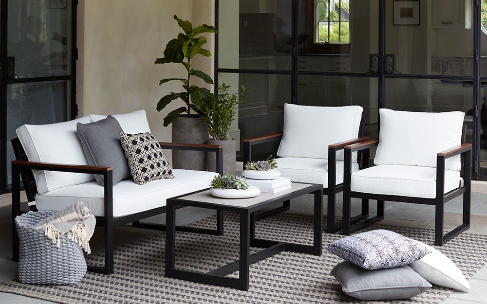 Black patio furniture with white cushions work in a