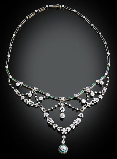 This stunning, classic Edwardian necklace is set with approximately 11.75 carats of shimmering white diamonds, while approximately 2.75 carats of vivid green emeralds and deep blue sapphires provide contrast and color.