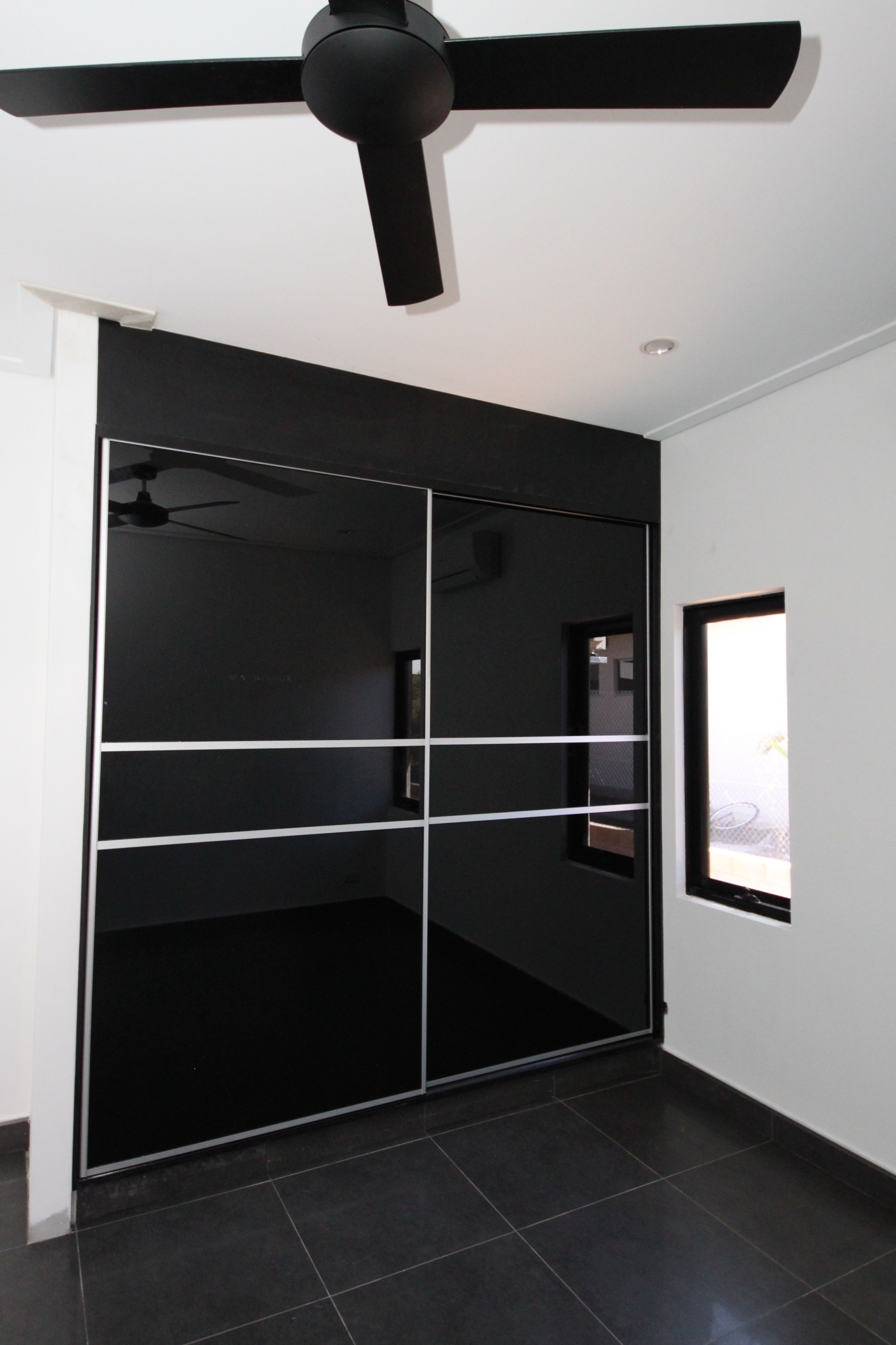 The Sliding Black Glass Doors In This Bedroom Compliment