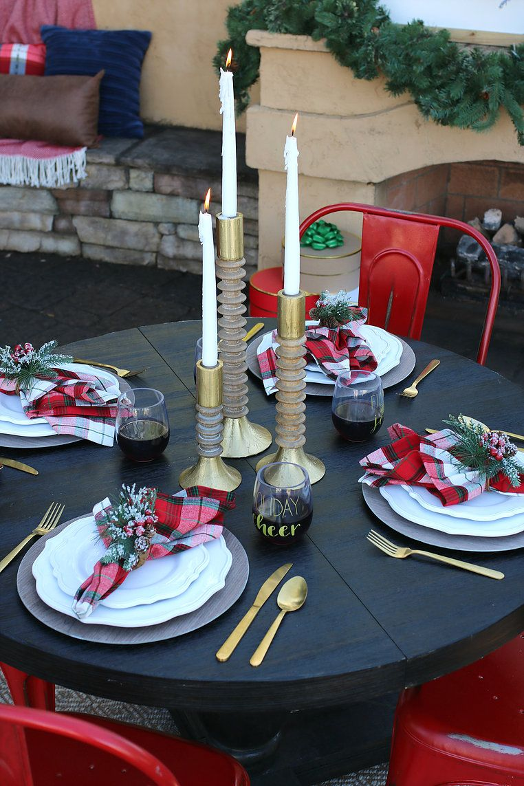 Holiday table setting with plaid, red, gold and green. Gold flatware adds glamour and the wood adds warmth to this rustic and traditional Christmas tablescape. I love the red metal chairs too!