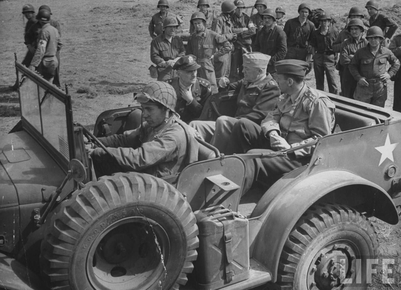 """GI's look on while Amer. Gen. Carl A. Spaatz speaks to Gen. Henry """"Hap"""" Arnold and Gen. Laurence S. Kuter who are seated in jeep during inspection of airfield while on US High Command tour of Normandy invasion area, June 15, 1944."""