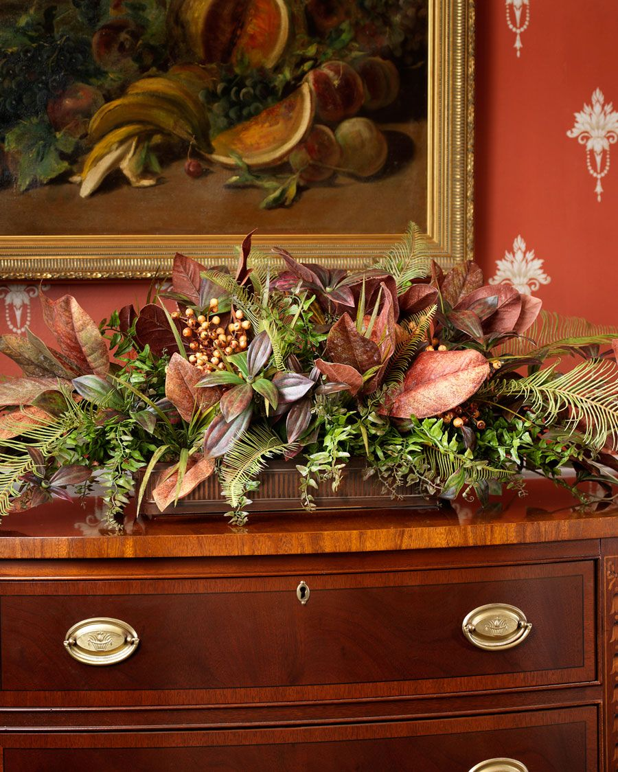 Low profile and high drama fall or Thanksgiving centerpiece. These Tuscan-colored silk magnolia leaves, golden berries, and two varieties of fern rest in a rectangular, aged brown metal planter.