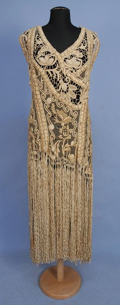 RIBBON EMBROIDERED LACE OVER-DRESS, c. 1920. Sleeveless ivory net decorated with heavy padded silk embroidery and French knots to below the hip, having a skirt of long ribbon fringe, back closure. B-40, W-34, L-56. (Some breaks to net and brides, loose ribbon pieces) good. $400-600.