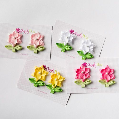 Danielle adds a soft touch to any hairstyle. She is created with two colors of ribbon, one for the stem and the other for the flower. The stem is available with polka dots or plain and the flower comes in a variety of colors.  Price: $10.50
