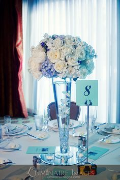 Blue and white wedding reception centerpiece with table placard ...