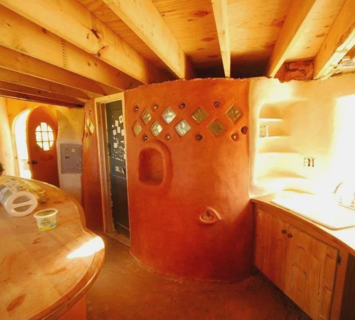 Here is another interior cob wall, this one separates a bathroom from the rest of a small artist & meditation studio in WV. This cob wall sits on tamped gravel & a waterproofing membrane to help eliminate any rising damp from getting into the sculpted clay wall.  https://www.facebook.com/photo.php?fbid=548960535128108=pb.171782289512603.-2207520000.1362045122=3