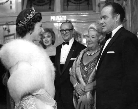 Queen Elizabeth II of Britain, left, chats with American comedian Bob Hope, right, and entertainer S... - AP