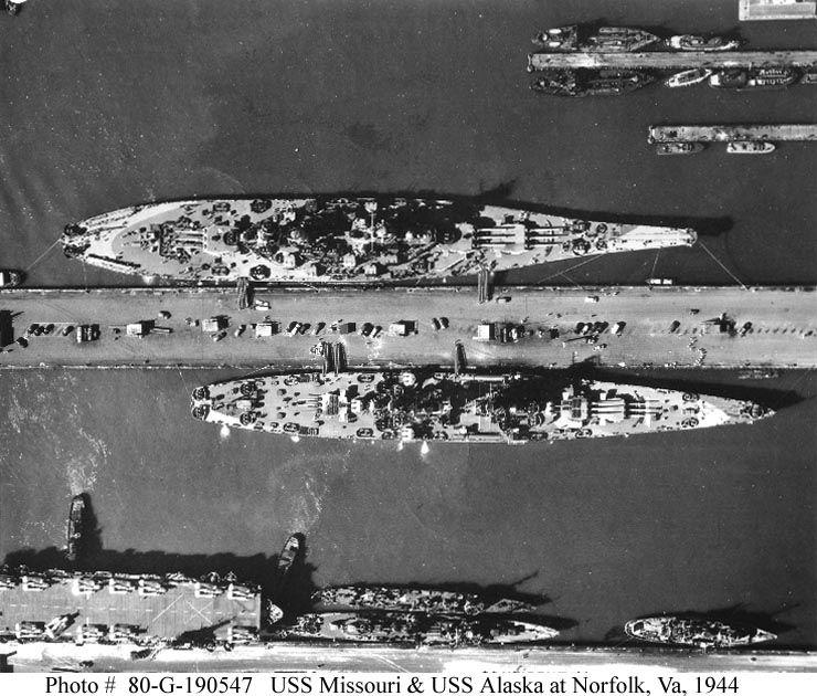 Aerial view of USS Missouri (BB-63) (top) and USS Alaska (CB-1) (bottom) pierside at Norfolk Navy Yard, 1944.