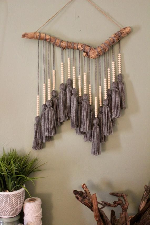 Beaded Gray Tassel Hanging is part of Macrame - This driftwood hanging can add texture to any empty wall or hang above a headboard in a bedroom  The driftwood foundation was found washed up on the coast of Florida near Fort Lauderdale beach  Yarn was individually measured, cut, and tied to create one single tassel  Small wooden beads were then added on top of each tassel then knotted to the top of the driftwood  After, yarn was tied to the driftwood to use for hanging  Product Details Driftwood Yarn Wooden beads Twine Measurements Width18 in Length 28 inches long from top of hanging to bottom of the fringe Custom orders are available upon request!