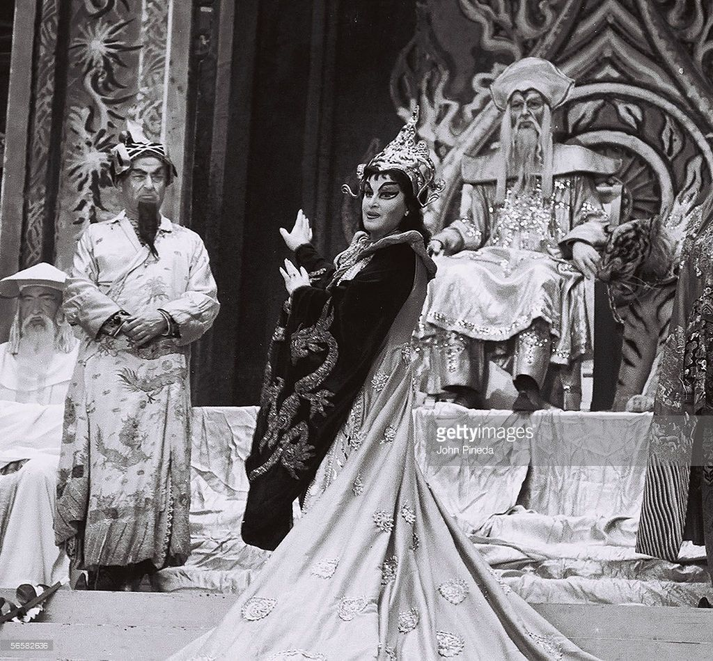 Swedish opera singer and soprano Birgit Nilsson (1918 - 2005), dressed in an elaborate traditional Chinese-inspired costume and stage makeup, performs as Princess Turandot in the opera 'Turandot' by Giacomo Puccini (1858 - 1924), 1962. The actor who portrays Emperor Altoum sits on his grand throne while fellow male cast members dressed in costume stand or sit nearby.