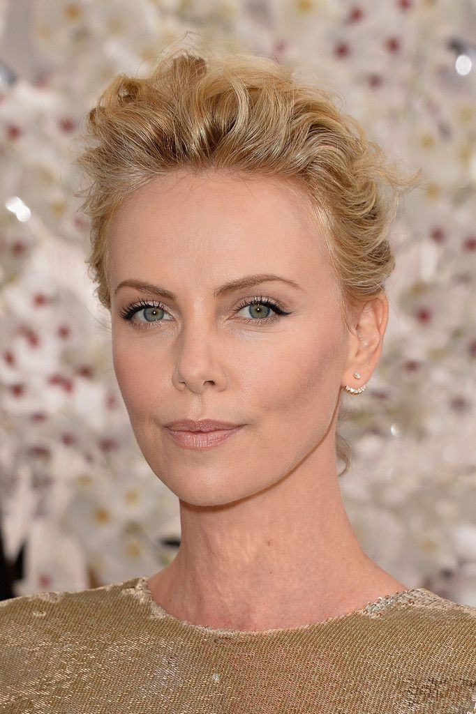 Celeb beauty - Charlize Theron looks stunning at the Christian Dior show - Paris Fashion Week 2014 with a tousled updo, black winged eyeliner and a nude lip.