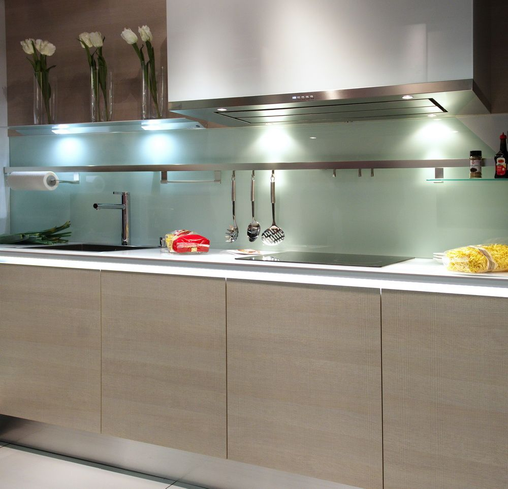 - Greige Cabinetry And Glass Backsplash In Sleek, Modern Style