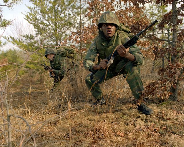 A pair of Marines armed with 5.56mm M16A1 rifles advance