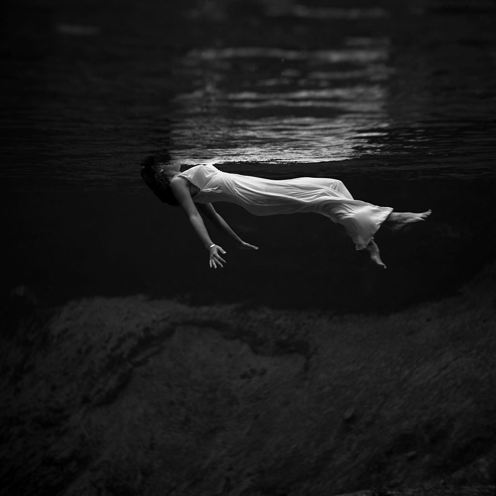 An underwater view of a woman, wearing a long gown, floating in water.    Photograph by World War II and fashion photographer Toni Frissell at Weeki Wachee Springs, Florida, USA, 1947